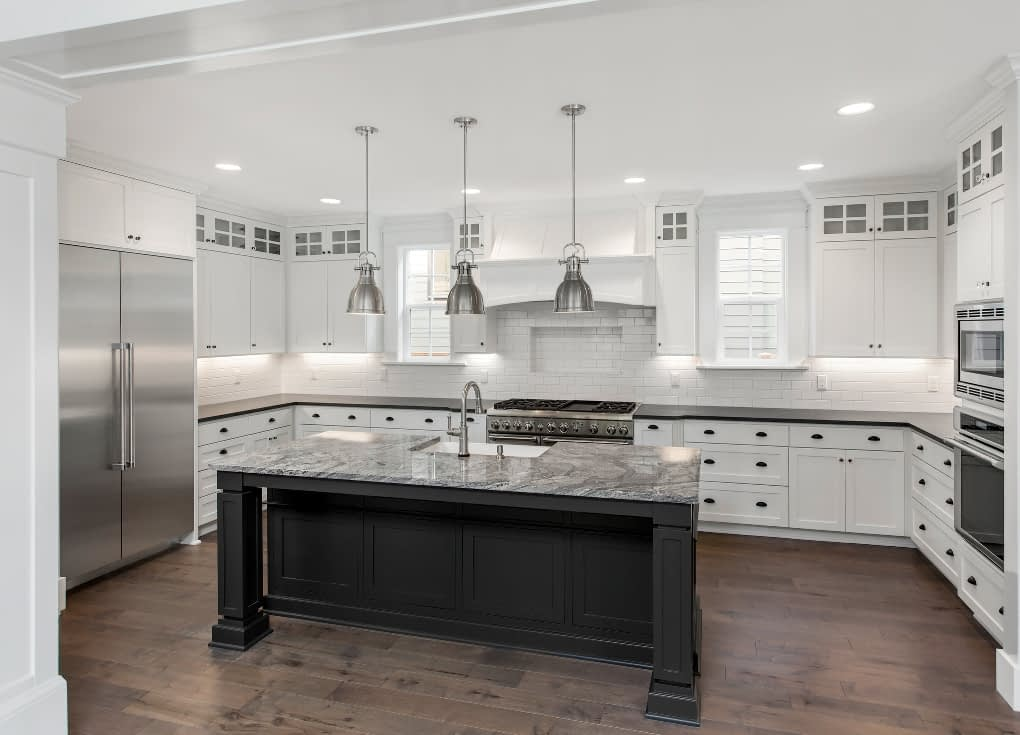 Transitional white custom kitchen cabinets and LVT plank flooring